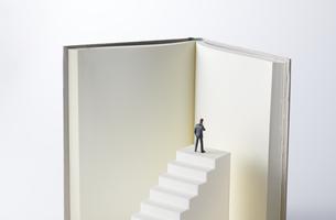 階段の頂上に上り本を読むビジネスマンの写真素材 [FYI04306023]