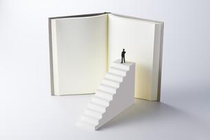 階段の頂上に上り本を読むミニチュアのビジネスマンの写真素材 [FYI04306025]