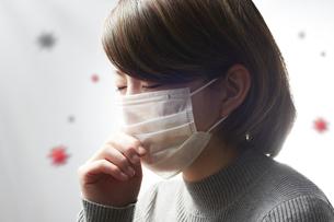 咳をするマスクをした女性の写真素材 [FYI04306031]