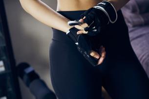 トレーニンググローブを着ける女性の手元の写真素材 [FYI04306050]