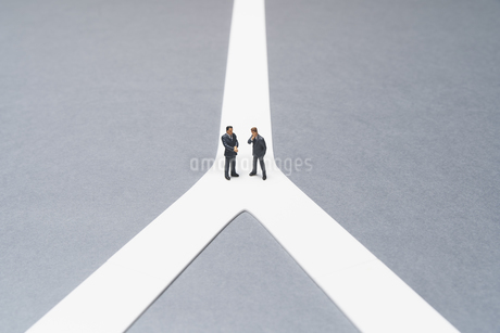 分かれ道の前の打ち合わせをするミニチュアのビジネスマンの写真素材 [FYI04306074]
