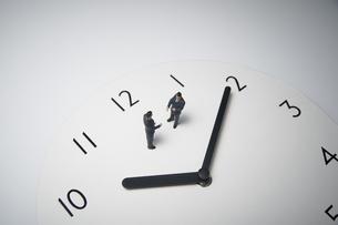 時計の上で打ち合わせするミニチュアのビジネスマンの写真素材 [FYI04306075]