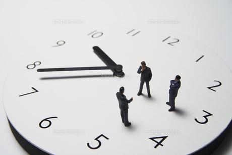 時計の上で話すミニチュアのビジネスマンの写真素材 [FYI04306076]