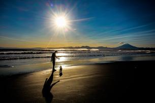 砂浜を歩く少年と犬の写真素材 [FYI04306090]