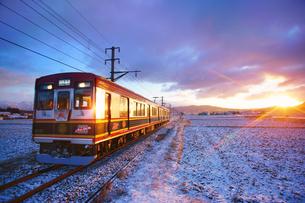 別所線のさなだどりーむ号と朝日と冬の田園の写真素材 [FYI04306414]
