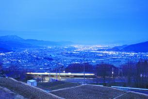 姨捨駅付近から望む長野方向の夜景とJR篠ノ井線の電車の写真素材 [FYI04306621]