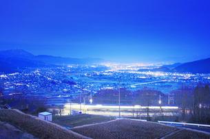 姨捨駅付近から望む長野方向の夜景とJR篠ノ井線の電車の写真素材 [FYI04306625]