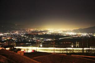 姨捨駅付近から望む長野方向の夜景とJR篠ノ井線の電車の軌跡の写真素材 [FYI04306636]
