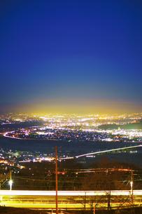 姨捨駅付近から望む長野方向の夜景とJR篠ノ井線の電車の軌跡の写真素材 [FYI04306638]