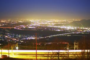姨捨駅付近から望む長野方向の夜景とJR篠ノ井線の電車の軌跡の写真素材 [FYI04306639]