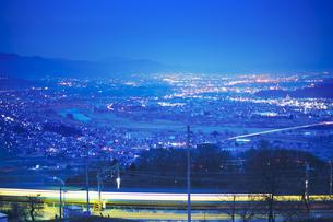 姨捨駅付近から望む長野方向の夜景とJR篠ノ井線の電車の軌跡の写真素材 [FYI04306645]