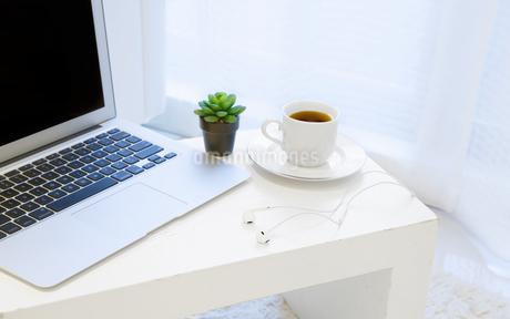 白いテーブルの上に置かれたノートパソコンとコーヒーの写真素材 [FYI04306849]
