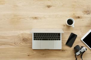 テーブルに置かれたノートパソコンとスマートフォンの写真素材 [FYI04307035]