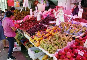 西營盤にある徳輔道西(デ・ヴォー・ロード・ウェスト)の「海味街」で売られる果物。世界各国から輸入されている。手前はアメリカのブドウ。奥は米国産サクランボの写真素材 [FYI04307231]