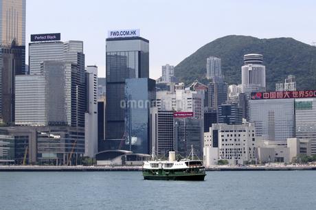 香港・ビクトリア湾を航行するスターフェリー。香港島と九龍半島の間で英国植民地時代から運行されている。後方は香港島の高層ビル群の写真素材 [FYI04307233]