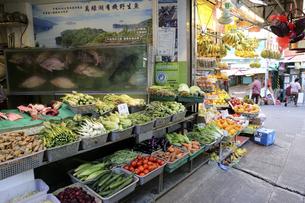 香港島・ワンチャイ(湾仔)の市場の魚屋兼八百屋。水槽の中の魚はハタ科の高級魚。蒸魚にして食べる事が多い。野菜は中国野菜だけでなく、トマトなどの西洋野菜も売っているの写真素材 [FYI04307235]