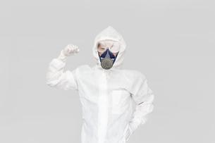防護服を着て片手でガッツポーズの男性。の写真素材 [FYI04307366]