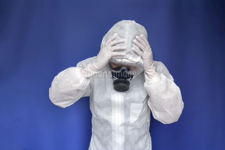伝染病の拡大に頭を抱える防護服の男性。新型ウィルス、パンデミック、医療崩壊、疲労イメージの写真素材 [FYI04307368]