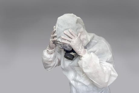 伝染病の拡大に頭を抱える防護服の男性。新型ウィルス、パンデミック、医療崩壊、疲労イメージの写真素材 [FYI04307369]