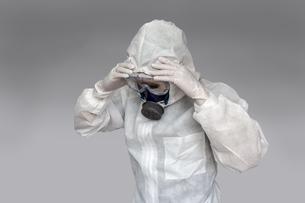 伝染病の拡大に頭を抱える防護服の男性。新型ウィルス、パンデミック、医療崩壊、疲労イメージの写真素材 [FYI04307370]