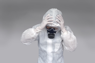 伝染病の拡大に頭を抱える防護服の男性。新型ウィルス、パンデミック、医療崩壊、疲労イメージの写真素材 [FYI04307371]