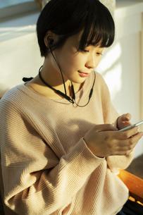 スマホを持ち音楽を楽しむ20代女性の写真素材 [FYI04307633]