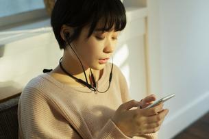 スマホを持ち音楽を楽しむ20代女性の写真素材 [FYI04307634]