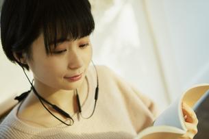 本を持ち音楽を楽しむ20代女性の写真素材 [FYI04307636]