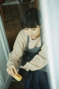 玄関先で靴磨きをする20代女性の写真素材 [FYI04307642]