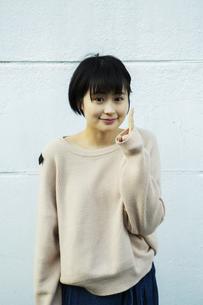 指さしをするカメラ目線の20代女性の写真素材 [FYI04307647]