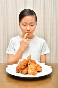 フライドチキンを食べる女の子の写真素材 [FYI04308499]