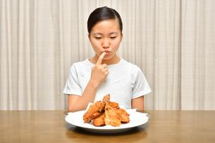フライドチキンを食べる女の子の写真素材 [FYI04308500]