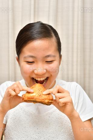 フライドチキンを食べる女の子の写真素材 [FYI04308501]
