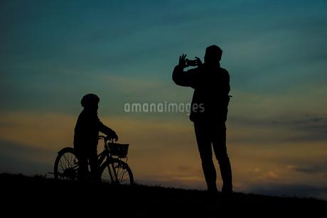 日没の丘に立つ親子のシルエットの写真素材 [FYI04308917]