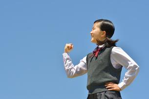 青空でガッツポーズをする女の子の写真素材 [FYI04310113]