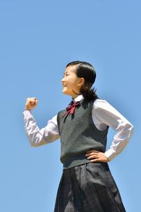 青空でガッツポーズをする女の子の写真素材 [FYI04310115]