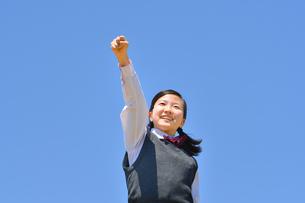 青空でガッツポーズをする女の子の写真素材 [FYI04310117]