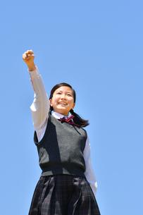 青空でガッツポーズをする女の子の写真素材 [FYI04310119]