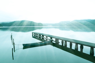 美しい光の中の湖畔の桟橋と船の写真素材 [FYI04310464]