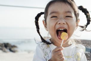 キャンディーを頬張り満面の笑みの少女の写真素材 [FYI04311537]