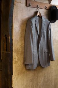 壁のコートハンガーにかけられたカシミアのジャケットとハットの写真素材 [FYI04311738]