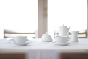 窓がある部屋で白いテーブルクロスの上に置かれた茶器の写真素材 [FYI04311740]