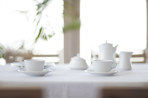 窓がある部屋で白いテーブルクロスの上に置かれた茶器の写真素材 [FYI04311741]