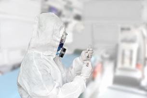防護服を身に着け治療室で注射器を手にする男性の写真素材 [FYI04311854]