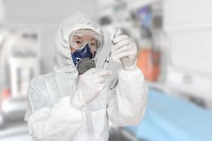 防護服を身に着け治療室で注射器を手にする男性の写真素材 [FYI04311855]