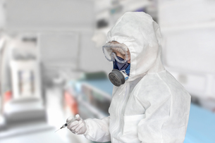 防護服を身に着け治療室で注射器を手にする男性の写真素材 [FYI04311857]