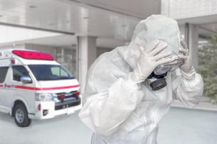 病院エントランスで救急車をバックに頭を抱える防護服の医療従事者の写真素材 [FYI04311859]