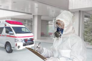 病院エントランスで救急車をバックに記録する防護服の男性の写真素材 [FYI04311860]