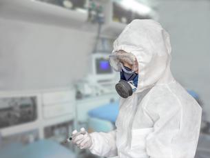 防護服を身に着け治療室で注射器を手にする男性の写真素材 [FYI04311862]