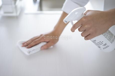 除菌スプレーで拭き掃除をする女性の手元の写真素材 [FYI04312120]